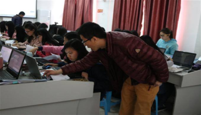 企业资深會計师在指导学生进行电脑做账